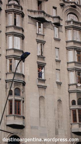 Mann beim Fensterstreichen im Palacio Salvo in Montevideo Uruguay
